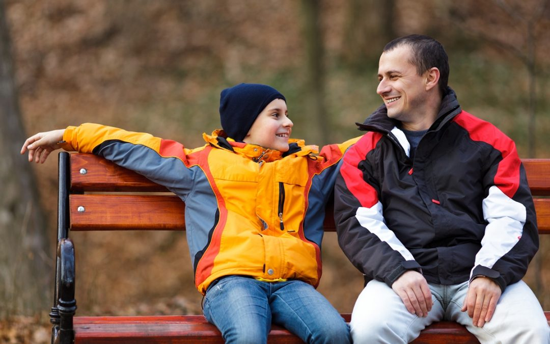 A father sitting on a bench with his son talking and giving praise
